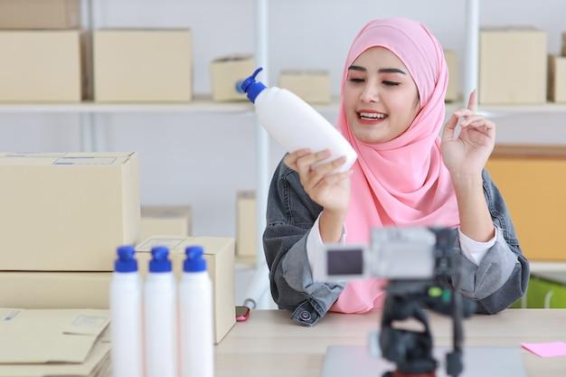 Joven activa blogger o vlogger de mujer musulmana asiática en chaqueta de jean mira a la cámara y habla en la filmación de video