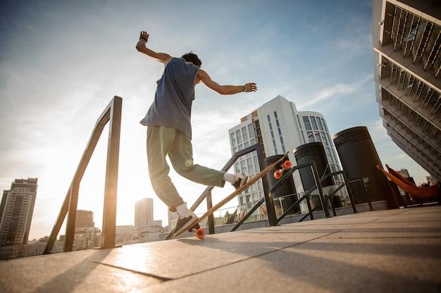 Joven activo saltando en patineta contra los edificios de la ciudad