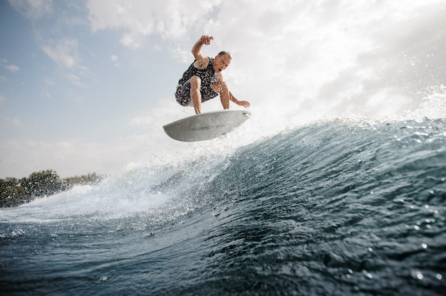 Joven activo saltando sobre el wakeboard blanco por el agua azul contra el cielo gris