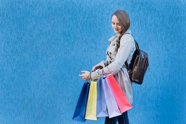 Joven adicto a las compras con bolsas de colores. pared de la calle azul