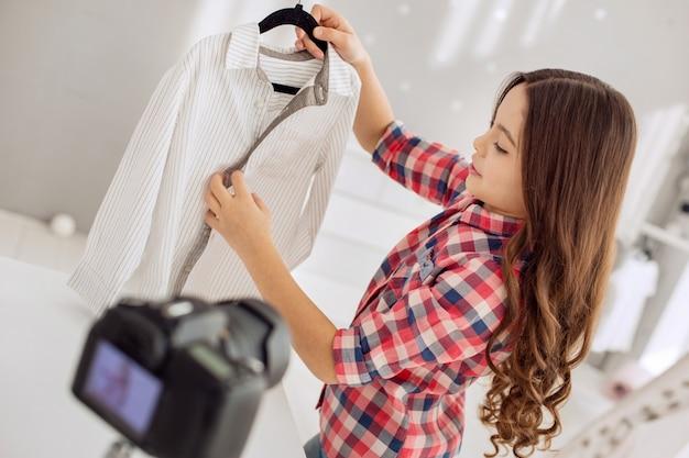 Joven adicto a las compras. encantadora pequeña preadolescente grabando un video blog de compras y hablando de su nueva camisa, después de haberla comprado recientemente