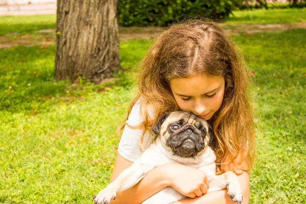 Joven adolescente abraza a su perro pug en el parque sobre la hierba verde