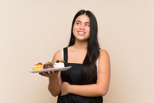 Joven adolescente asiática chica sosteniendo un montón de diferentes mini tortas sobre pared aislada mirando hacia arriba mientras sonríe
