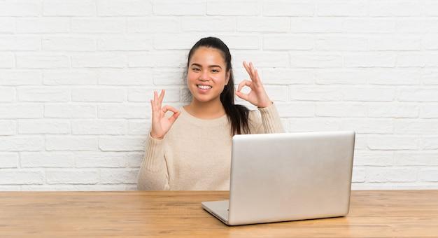 Joven adolescente asiática con una computadora portátil en una mesa mostrando un signo bien con los dedos