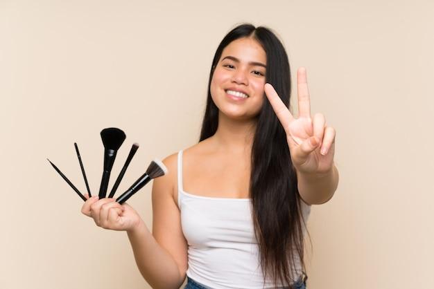 Joven adolescente asiática sosteniendo una gran cantidad de pincel de maquillaje sonriendo y mostrando el signo de la victoria