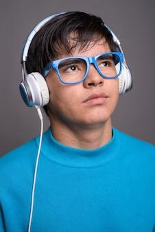 Joven adolescente asiático escuchando música contra backgrou gris
