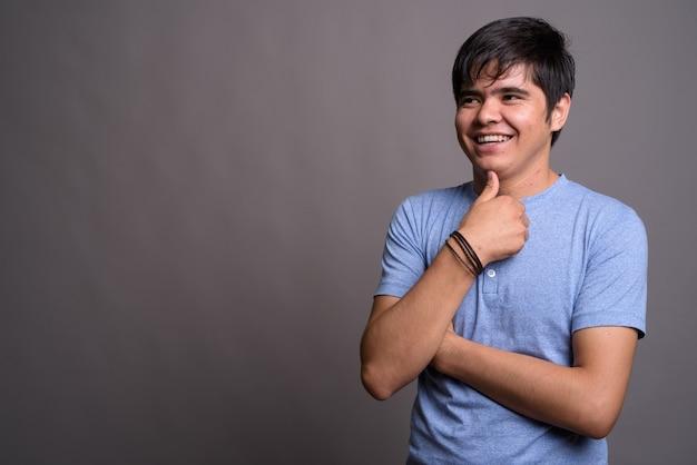 Joven adolescente asiático vistiendo la camiseta azul contra la pared gris