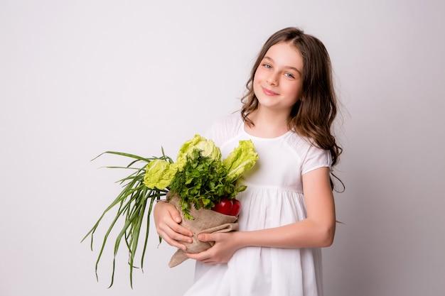 Joven adolescente con una bolsa de verduras