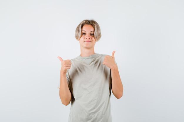Joven adolescente en camiseta mostrando doble pulgar hacia arriba y mirando orgulloso, vista frontal.