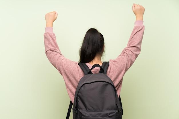 Joven adolescente chica asiática sobre fondo verde aislado con mochila