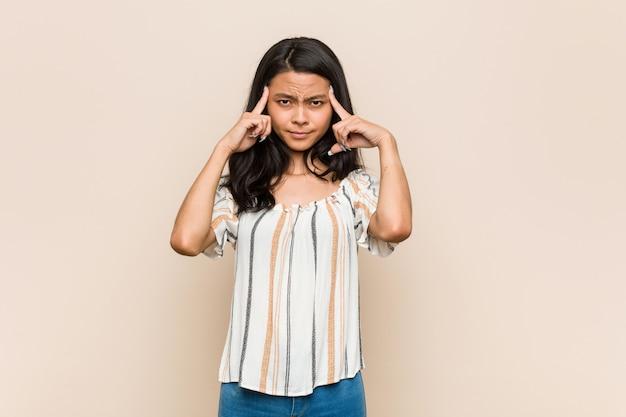 Joven adolescente chino lindo joven mujer rubia con un abrigo contra un fondo rosa se centró en una tarea, manteniendo los dedos índice apuntando a la cabeza.