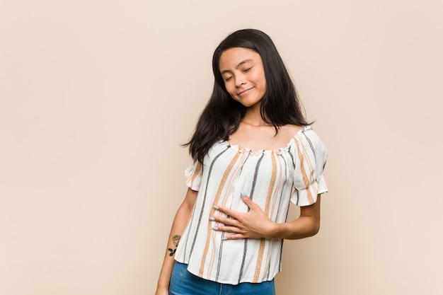Joven adolescente chino lindo joven mujer rubia con un abrigo contra un fondo rosa toca el estómago, sonríe suavemente, comer y concepto de satisfacción.