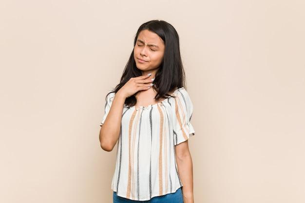 Joven adolescente chino lindo joven mujer rubia con un abrigo contra una pared rosa sufre dolor en la garganta debido a un virus o infección.