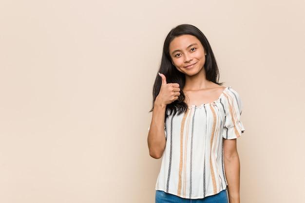 Joven adolescente chino lindo joven mujer rubia vistiendo un abrigo contra una pared rosa sonriendo y levantando el pulgar hacia arriba
