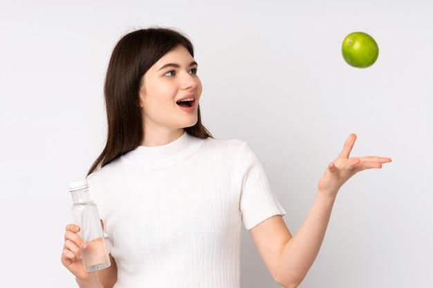 Joven adolescente con una manzana y con una botella de agua