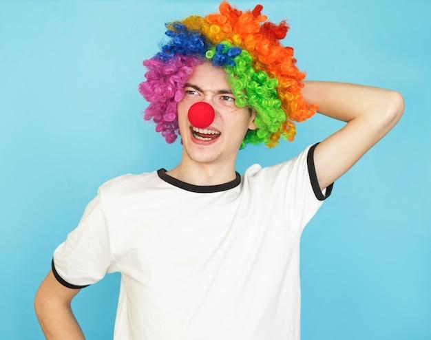 Joven adolescente masculino divertido en camiseta blanca sobre fondo azul.
