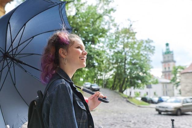 Joven adolescente bajo un paraguas en la calle de la ciudad