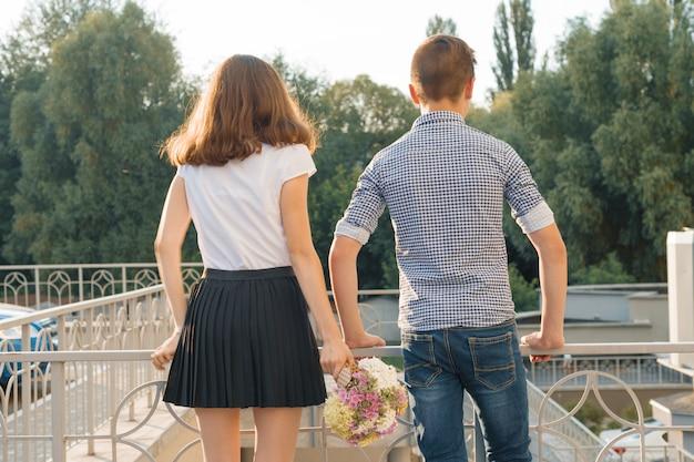 Joven adolescente pareja niño y niña de pie atrás, día soleado de verano