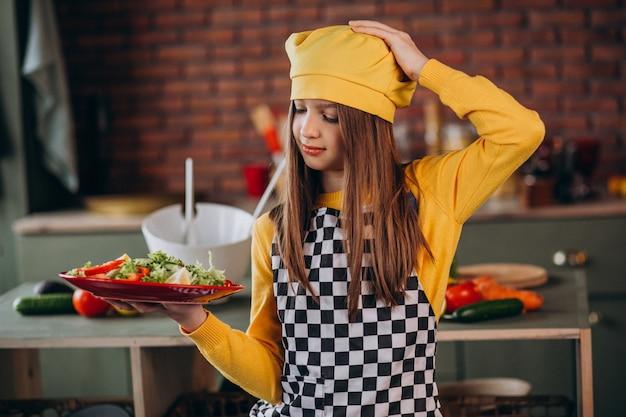 Joven adolescente preparando ensaladas para el desayuno en la cocina