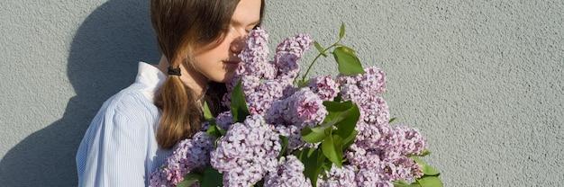 Joven adolescente con ramo de lilas cerca de la pared gris