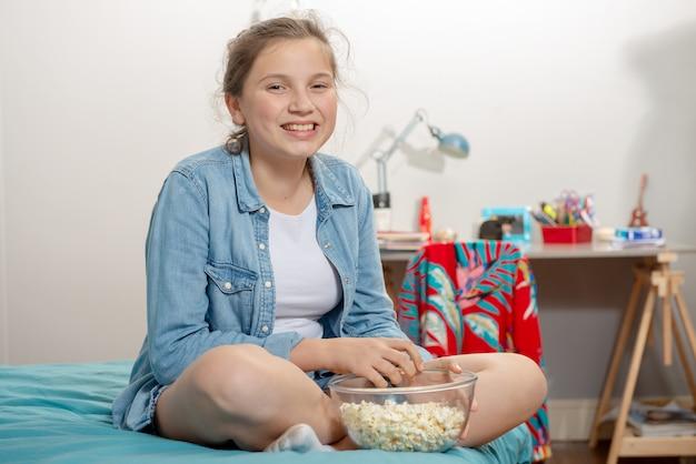 Joven adolescente sentada en la cama comiendo palomitas de maíz