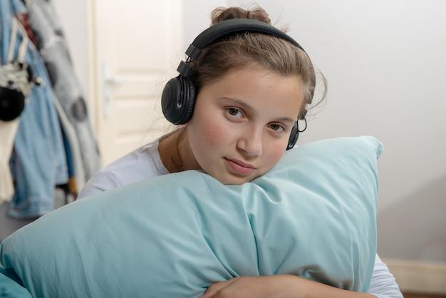 Joven adolescente sentada en la cama en el dormitorio escuchar música con auriculares