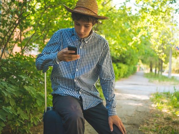 Joven adolescente en un sombrero casual y de verano sentado en una bolsa de viaje y en un teléfono de desplazamiento