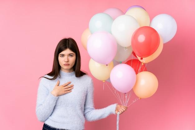 Joven adolescente sosteniendo muchos globos sobre pared rosa suplicando