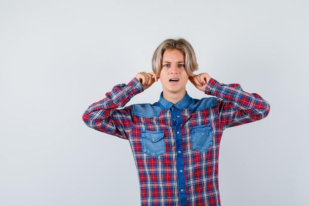Joven adolescente tirando hacia abajo de los lóbulos de las orejas en camisa a cuadros y mirando asustado