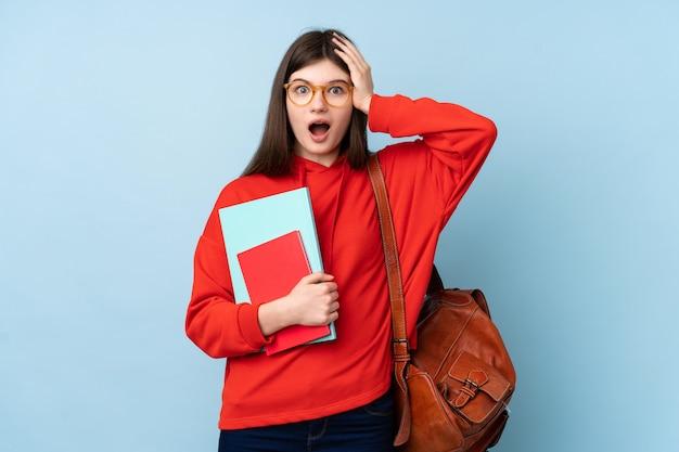 Joven adolescente ucraniana estudiante mujer sosteniendo una ensalada sobre la pared azul aislada con expresión facial sorpresa