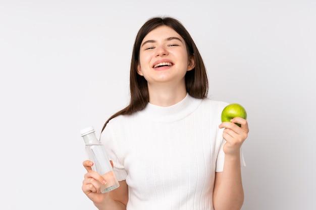 Joven adolescente ucraniana sobre pared blanca aislada con una manzana y con una botella de agua