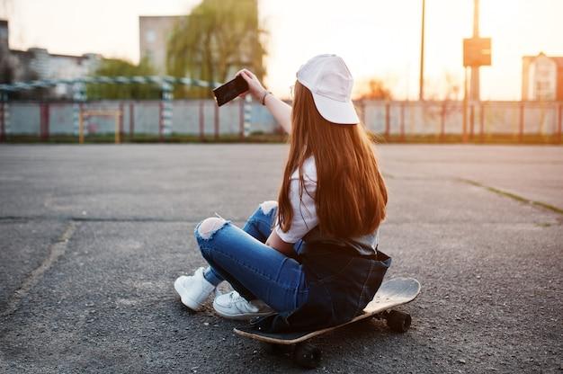 Joven adolescente urbana con patineta, usar anteojos, gorra y jeans rotos en el campo de deportes del patio en la puesta de sol haciendo selfie en el teléfono.