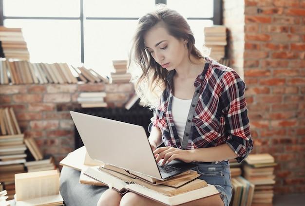 Joven adolescente usando la computadora portátil rodeada de muchos libros.