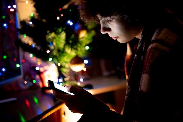 Joven adolescente usando el teléfono inteligente en la noche de navidad en casa cerca del árbol.