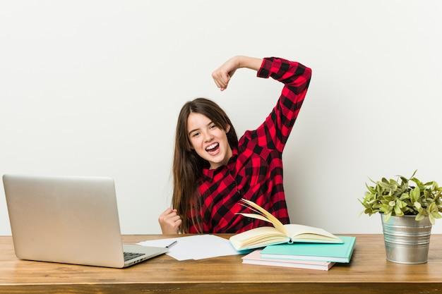 Joven adolescente volviendo a su rutina haciendo la tarea levantando el puño después de una victoria.