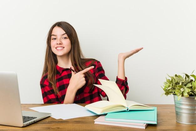 Joven adolescente volviendo a su rutina haciendo tareas emocionadas sosteniendo un espacio de copia en la palma.