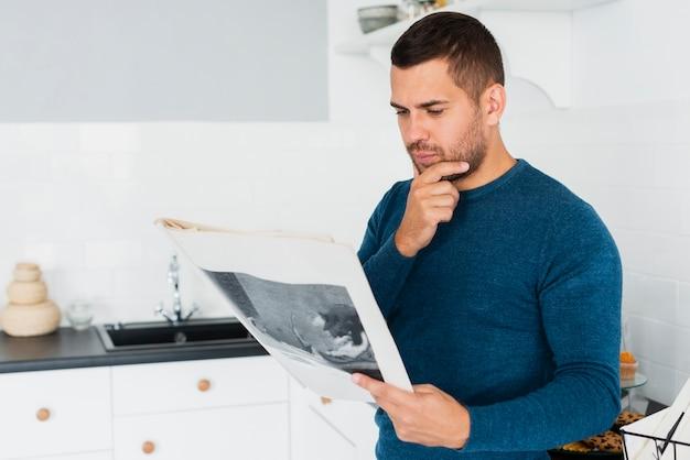 Joven adulto está leyendo el periódico en la cocina