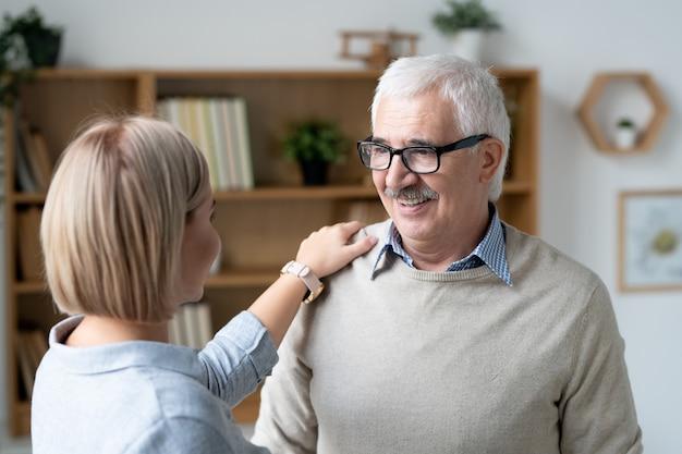 Joven afectuosa manteniendo la mano sobre el hombro de su padre feliz mientras habla en el entorno hogareño