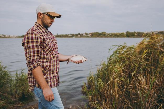 Joven sin afeitar con camisa a cuadros, gorra y gafas de sol atrapó un pez y lo sostiene en brazos en la orilla del lago en el fondo de agua, arbustos y cañas. estilo de vida, recreación de pescadores, concepto de ocio