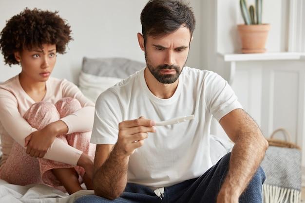 El joven sin afeitar disgustado sostiene la prueba de embarazo, se siente estresado por los resultados positivos, espera un bebé no deseado. mujer disgustada se sienta detrás.