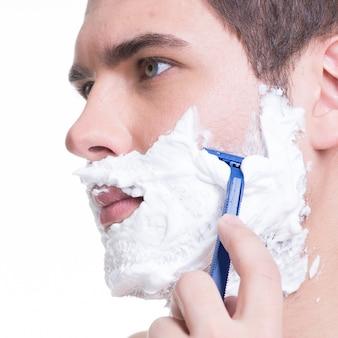 Joven afeitarse la barba con la navaja