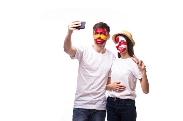 Joven aficionado al fútbol español y croata tomar selfie aislado en la pared blanca