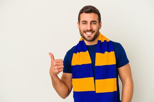 Joven aficionado caucásico de un equipo de fútbol aislado sobre fondo blanco sonriendo y levantando el pulgar hacia arriba