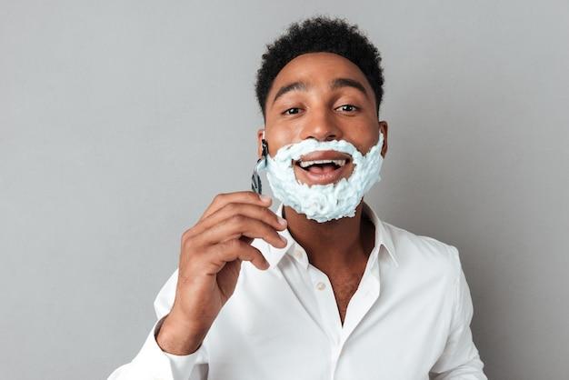 Joven africana en camisa de afeitar con una navaja de afeitar