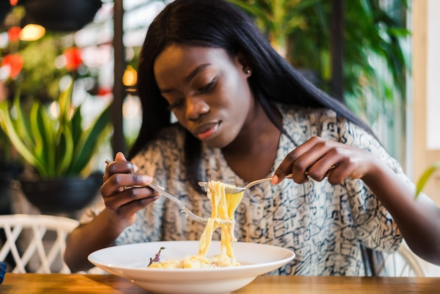 Joven africana comiendo espaguetis en restaurante.