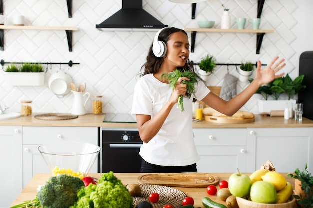 Joven africana emocional está escuchando música a través de auriculares y tiene eneldo