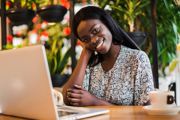 Joven africana emplazamiento en el café trabajando en equipo portátil