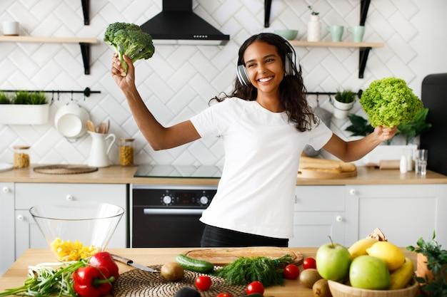 Joven africana está feliz escuchando música a través de auriculares y sostiene un brócoli y ensalada