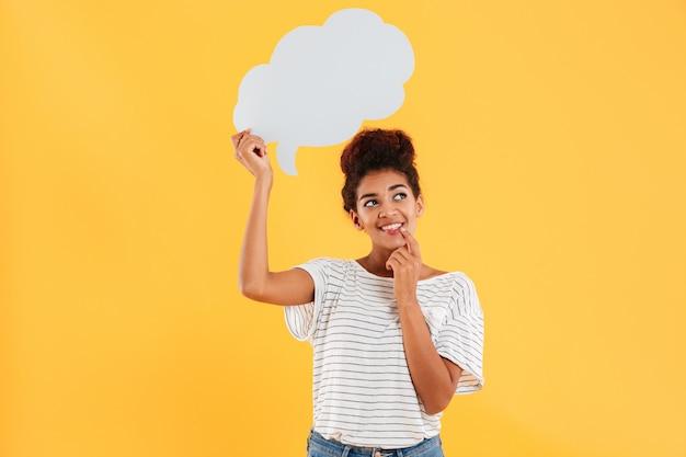 Joven africana feliz pensativa dama mirando hacia arriba y sosteniendo el bocadillo en blanco aislado sobre amarillo