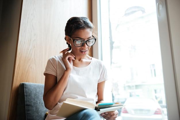 Joven africana con gafas sentado en la biblioteca